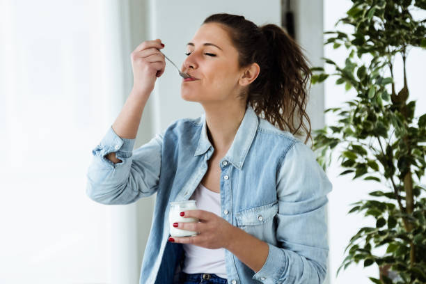 Beautiful young woman eating yogurt at home. stock photo