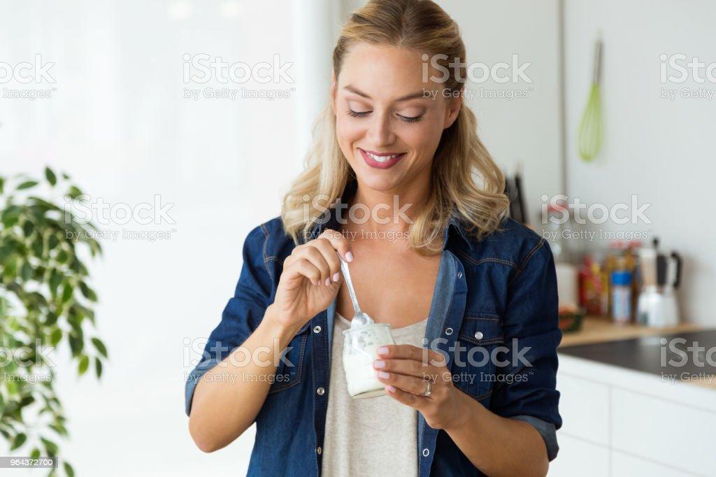 Bela jovem comendo iogurte em casa. - Foto de stock de Adulto royalty-free