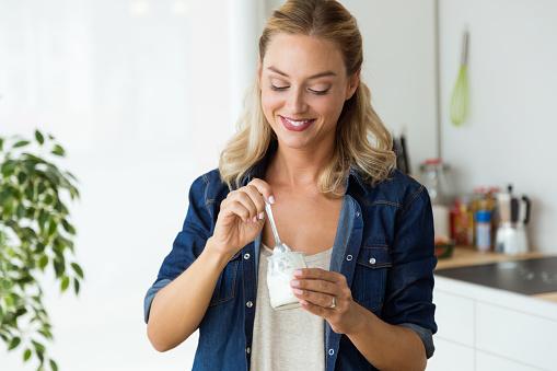Foto de Bela Jovem Comendo Iogurte Em Casa e mais fotos de stock de Adulto