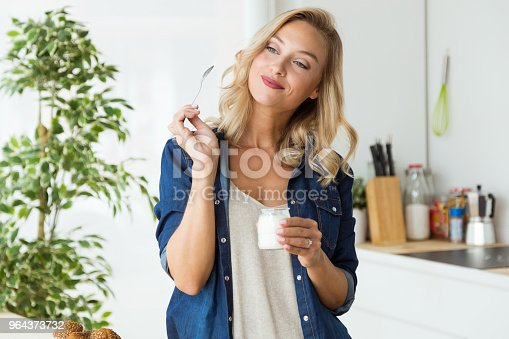 istock Beautiful young woman eating yogurt at home. 964373732