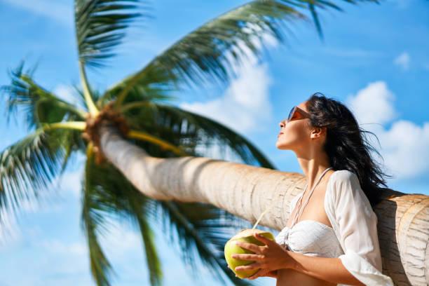 Schöne junge Frau genießen Kokosnuss-Drink und entspannen am tropischen Strand mit Palme – Foto