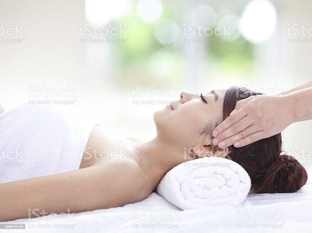 Beautiful young woman enjoy receiving face massage stock photo