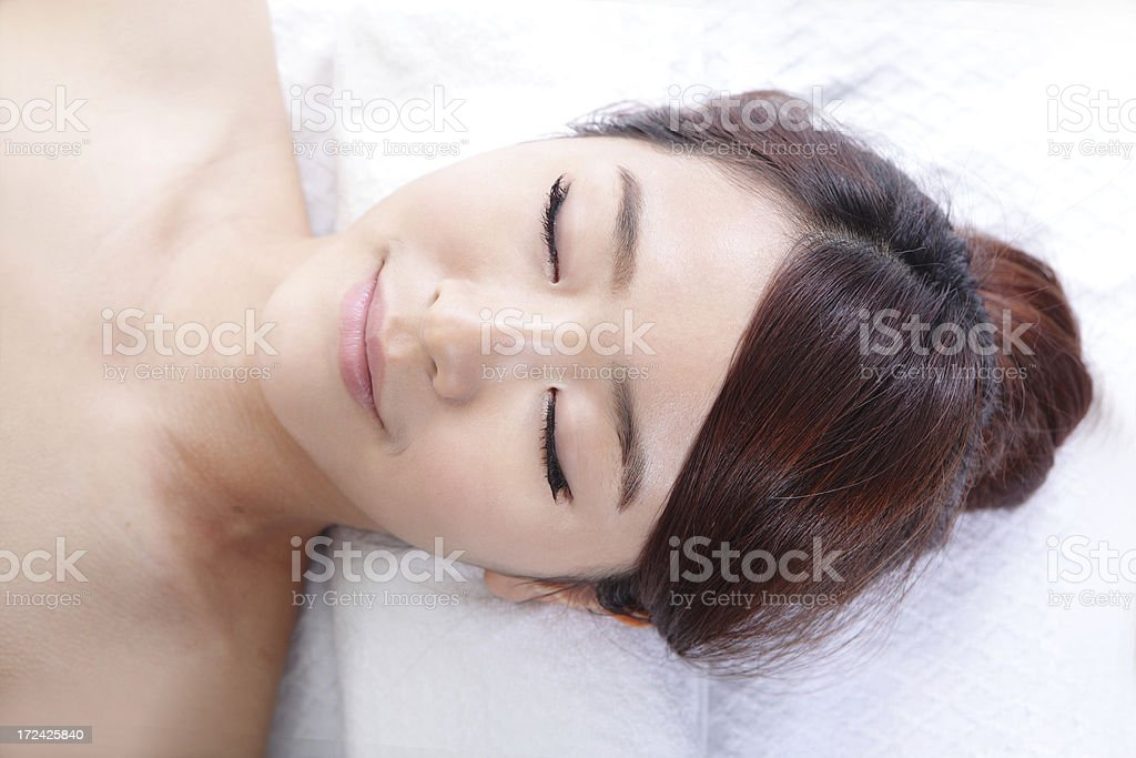 Beautiful young woman enjoy receiving face massage royalty-free stock photo