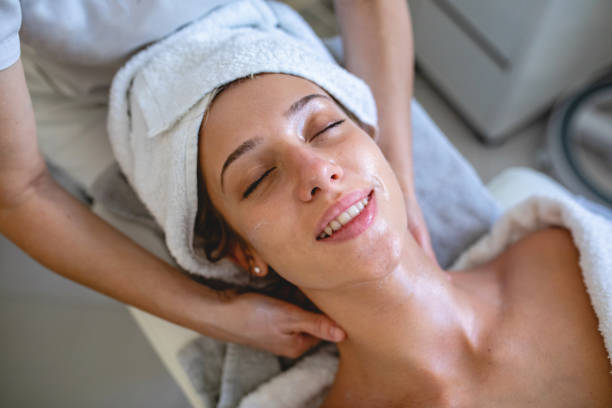 Beautiful young woman enjoying a massage at a spa stock photo