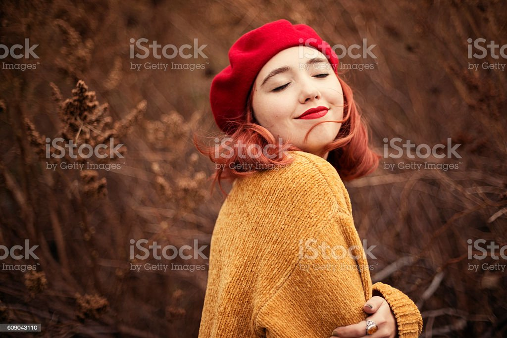 Beautiful young woman enjoying autumn wind in nature. stock photo