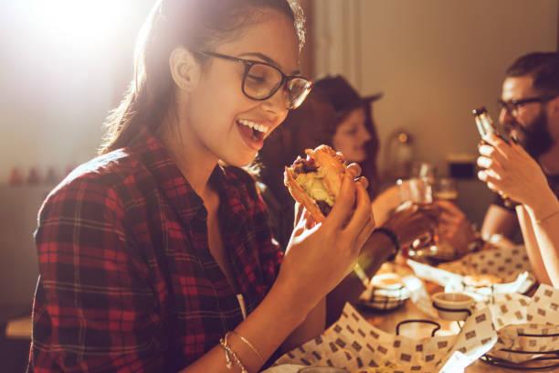 beautiful young woman enjoying her burger stock photo