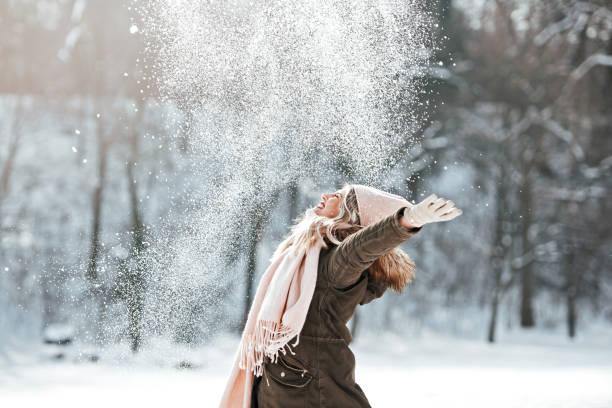 Beautiful young woman enjoying in the snow stock photo
