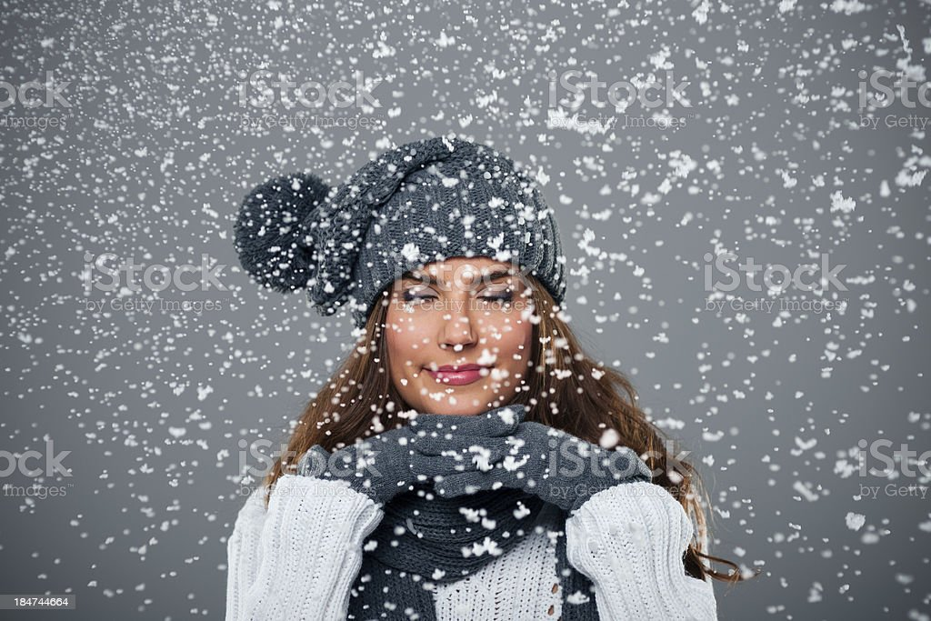 Beautiful young woman enjoys first snow royalty-free stock photo