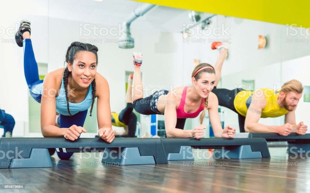 Beautiful young woman exercising a plank variation during group workout class royalty-free stock photo