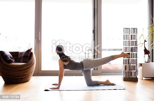 Beautiful young woman working out at home in living room, doing yoga or pilates exercise.