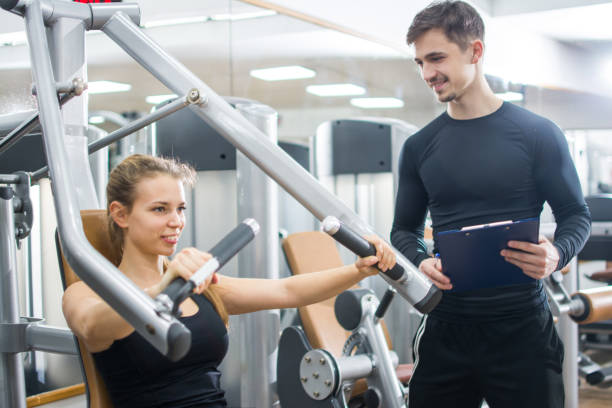 Beautiful young woman exercising on exercise machine with help by personal trainer in gym. Beautiful young woman exercising on exercise machine with help by personal trainer in gym. exercise machine stock pictures, royalty-free photos & images