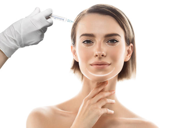beautiful young woman face and hand in glove with syringe making injection stock photo