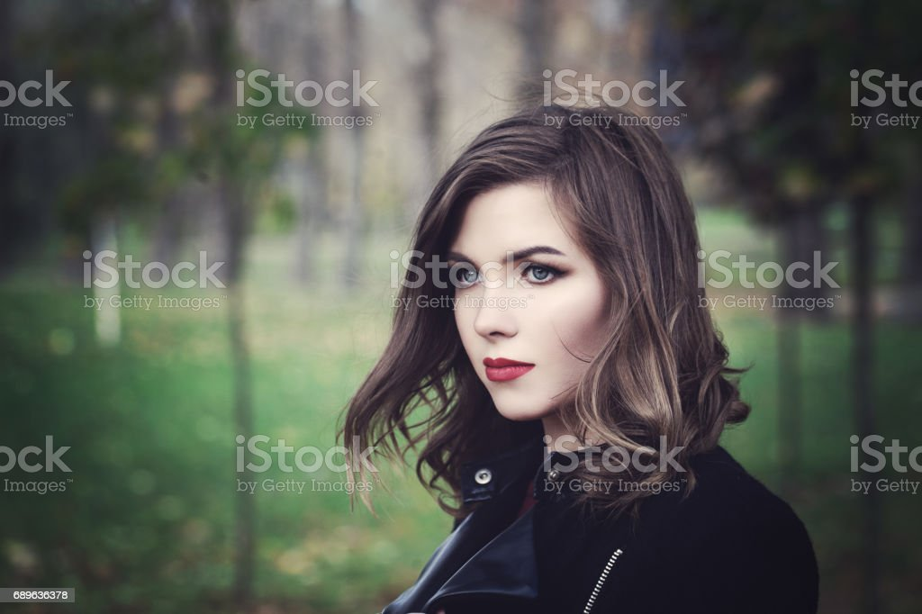 Beautiful Young Woman Fashion Model Walking in the Park. Outdoors Portrait stock photo