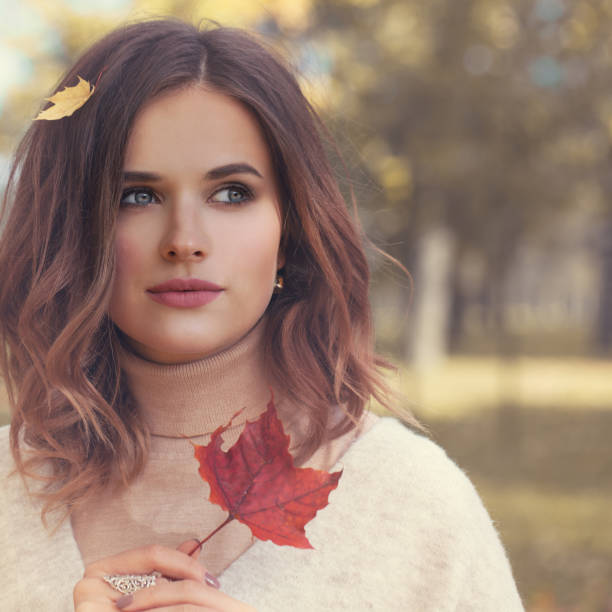 Beautiful Young Woman Fashion Model with Red Fall Mapple Leaf Outdoors, Autumn Beauty stock photo