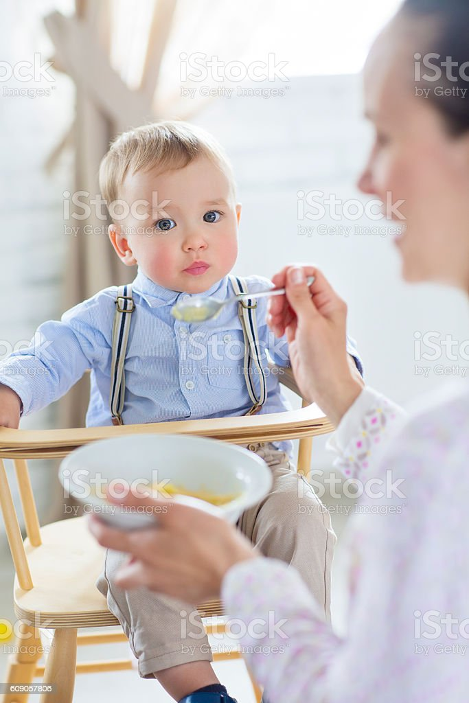 Beautiful young woman feeds her baby son – Foto