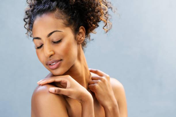 Beautiful young woman feeling soft skin stock photo