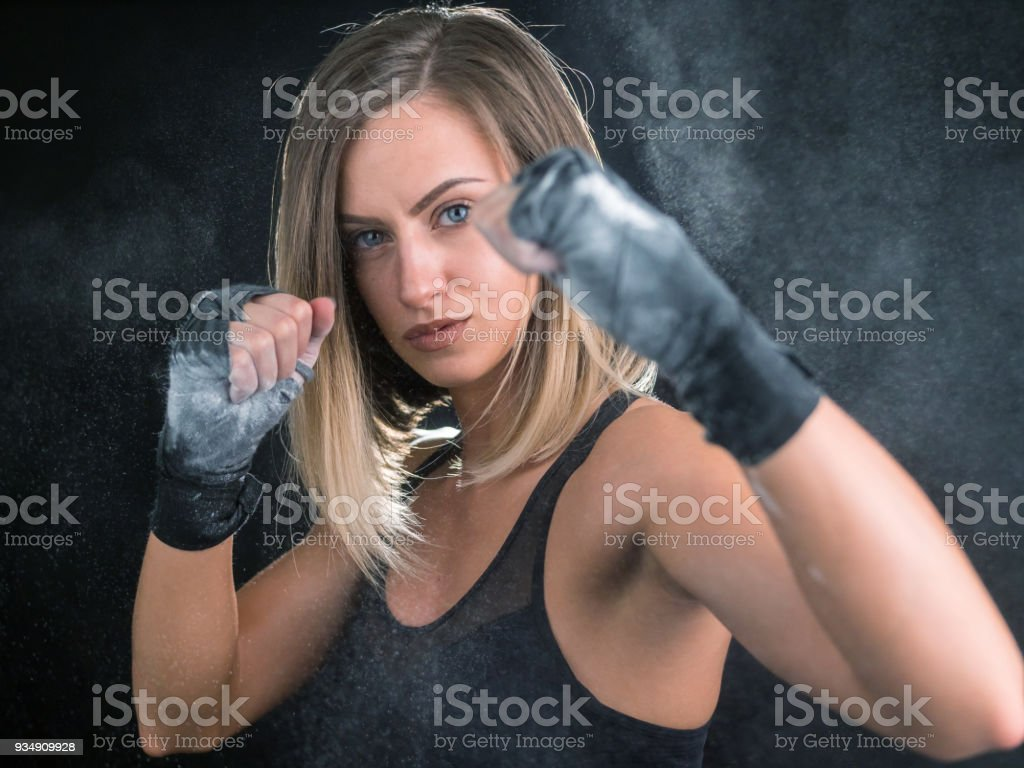 Beautiful young woman fighter with bandaged hands looking at camera stock photo