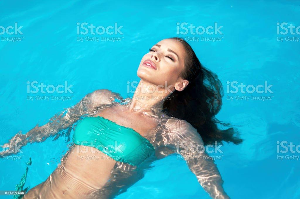 Schöne junge Frau, die schwimmend im pool – Foto