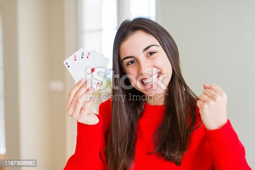 Beautiful young woman gambling playing poker screaming proud and celebrating victory and success very excited, cheering emotion
