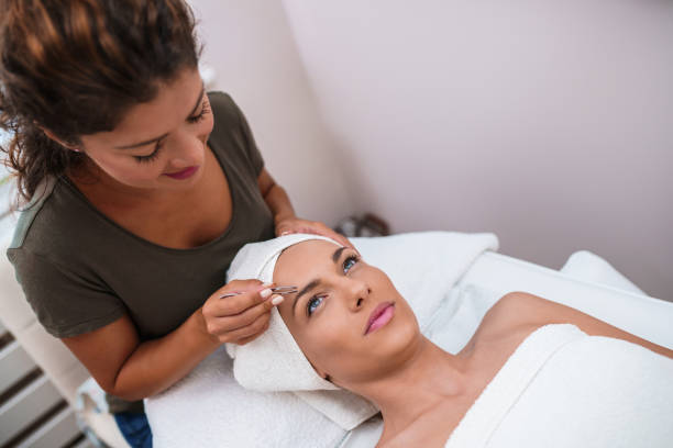 Beautiful young woman gets eyebrow correction procedure stock photo