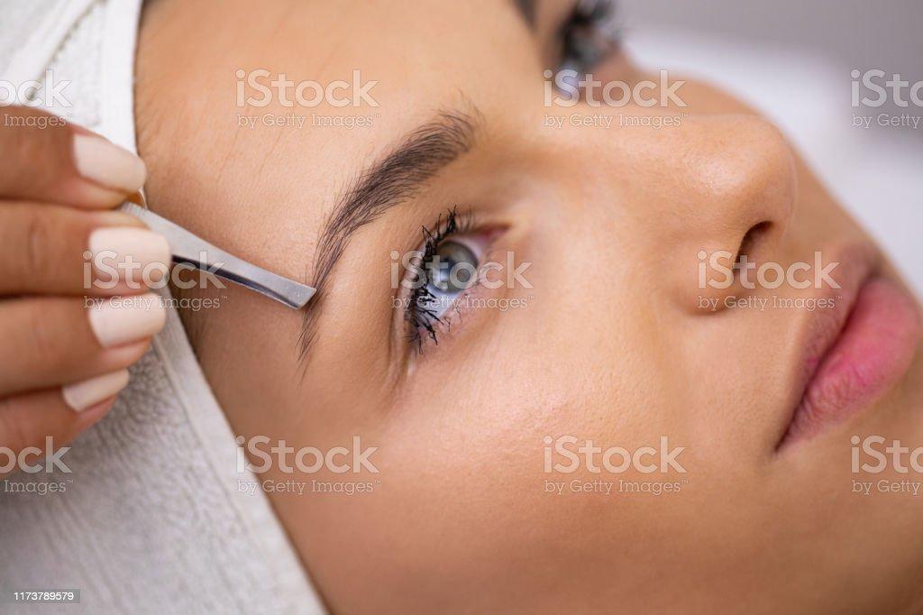 Schöne junge Frau bekommt Augenbrauen Korrektur Verfahren - Lizenzfrei Auge Stock-Foto