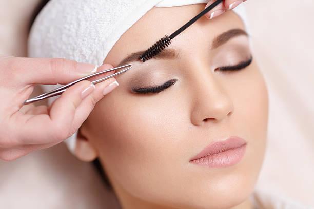 Beautiful young woman gets eyebrow correction procedure - Photo