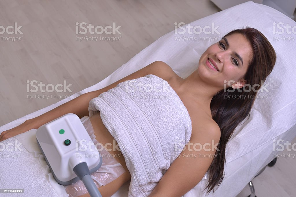 Beautiful young woman getting cryolipolyse treatment in cosmetic stock photo