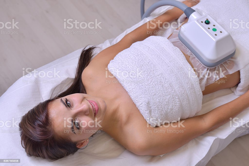 Beautiful young woman getting cryolipolyse treatment in cosmetic cabinet stock photo
