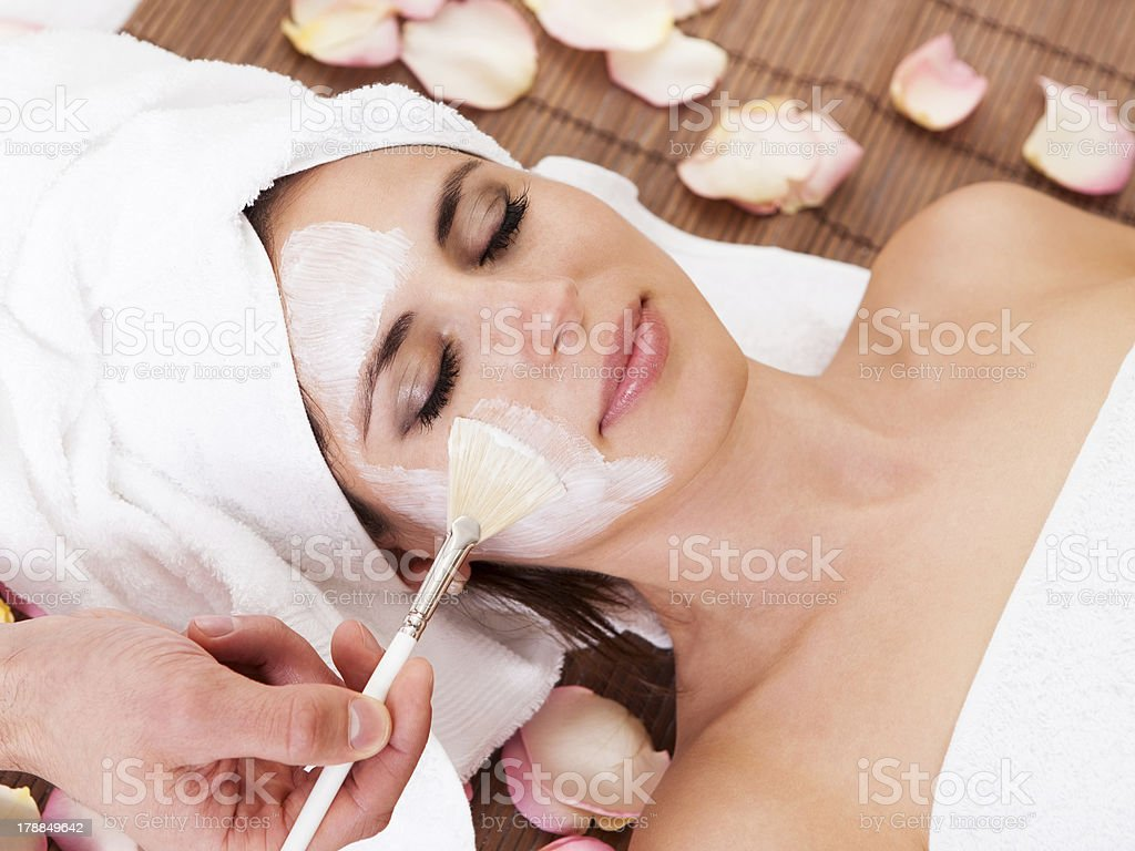 Beautiful young woman getting facial mask royalty-free stock photo
