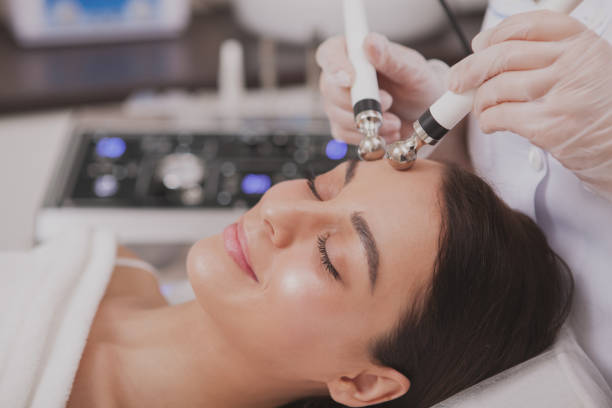 Beautiful young woman getting facial skincare treatment Close up of a lovely relaxed young woman enjoying facial microcurrent therapy by professional cosmetologist. Beautiful woman with perfect skin getting face care procedures by beautician tighten stock pictures, royalty-free photos & images