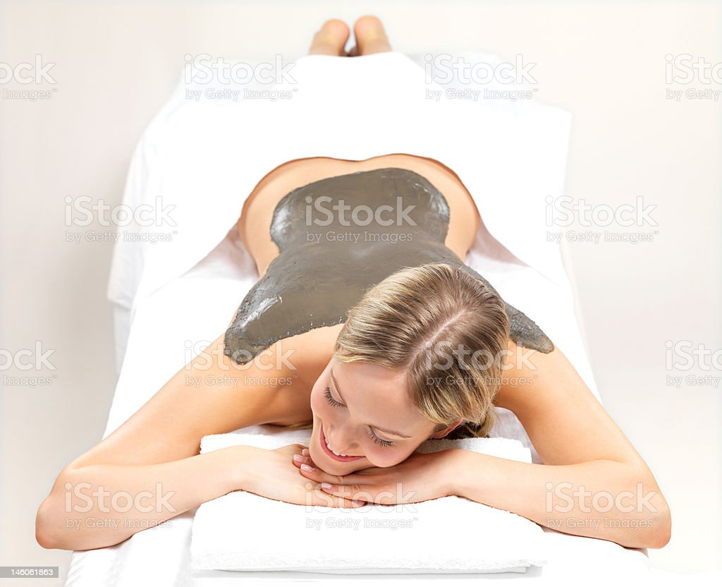 Beautiful young woman getting mud skin treatment at day spa royalty-free stock photo