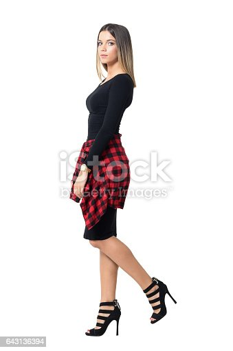Side view of beautiful young woman graceful posing with one leg raised up. Full body length isolated over white studio background.