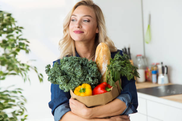 beautiful young woman grocery shopping bag with vegetables at home. - bio food foto e immagini stock