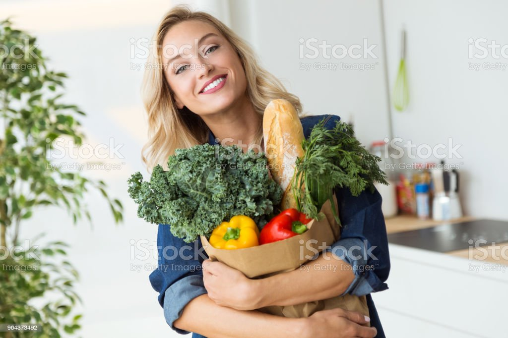 Mulher jovem e bonita sacola de compras de supermercado com legumes em casa. - Foto de stock de Adulto royalty-free