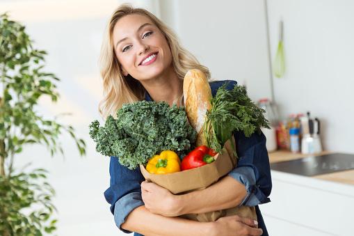Foto de Mulher Jovem E Bonita Sacola De Compras De Supermercado Com Legumes Em Casa e mais fotos de stock de Adulto