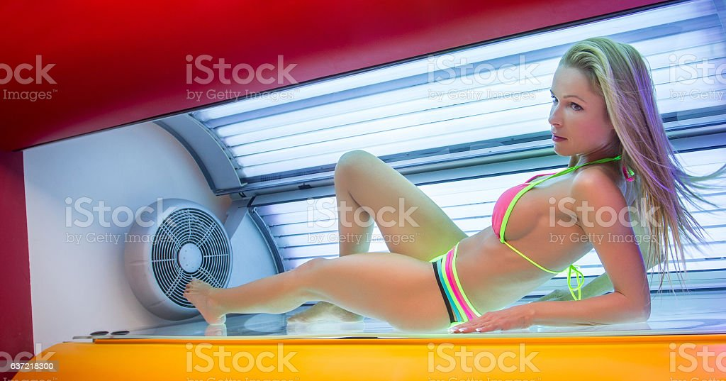 Beautiful young woman have tanning skin treatment in modern sola stock photo