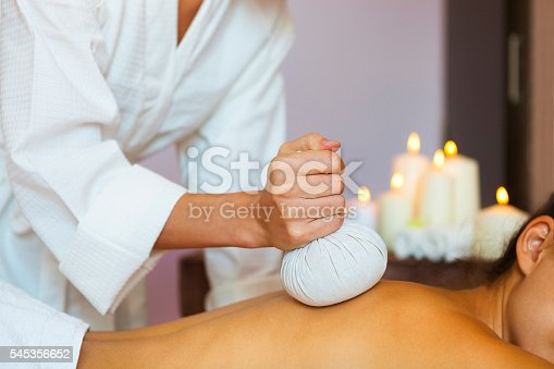 istock Beautiful young woman having back massage with pouch of rice 545356652