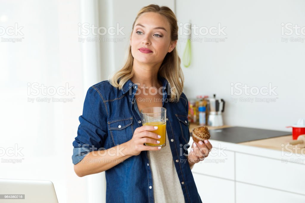 Mulher jovem e bonita tomando café na cozinha. - Foto de stock de Adulto royalty-free