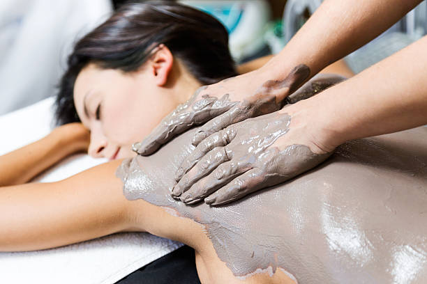 beautiful young woman having clay body mask apply by beautician. - błoto zdjęcia i obrazy z banku zdjęć
