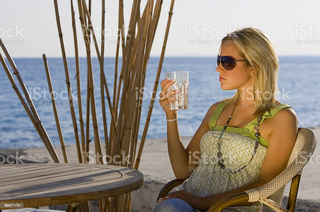 Beautiful Young Woman Having Evening Drink By the Sea royalty-free stock photo