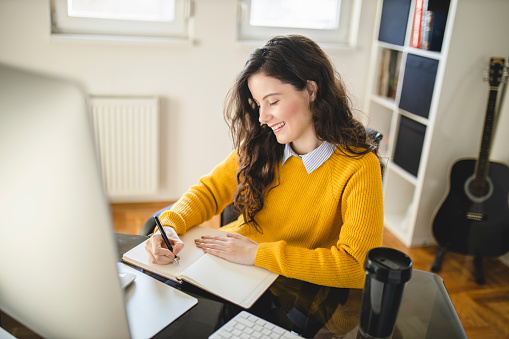 Beautiful young woman having online class and learning at home