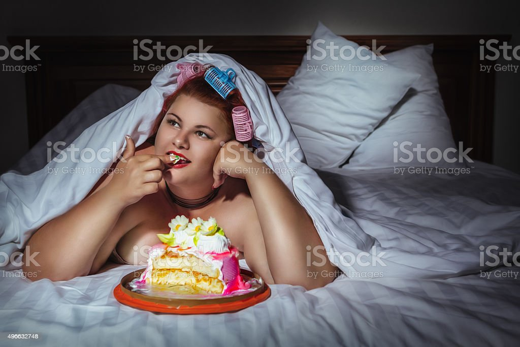 Beautiful young woman hiding under the blanket and eating cookie stock photo