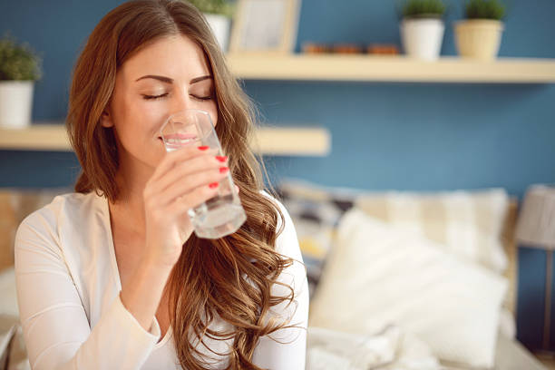 beautiful young woman holding a glass of water - woman water stockfoto's en -beelden