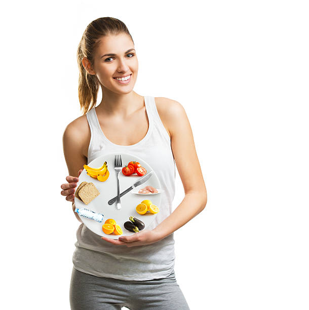 Beautiful young woman holding a plate with food stock photo
