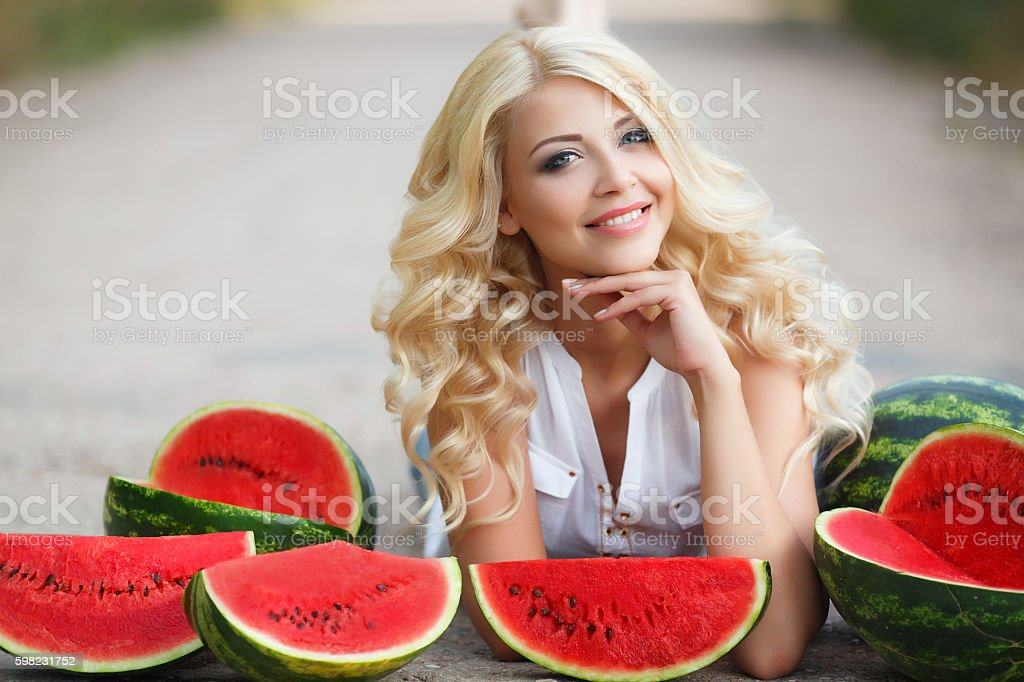 Beautiful young woman holding a slice of ripe watermelon foto royalty-free