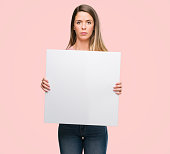 istock Beautiful young woman holding advertising banner with a confident expression on smart face thinking serious 1044769780