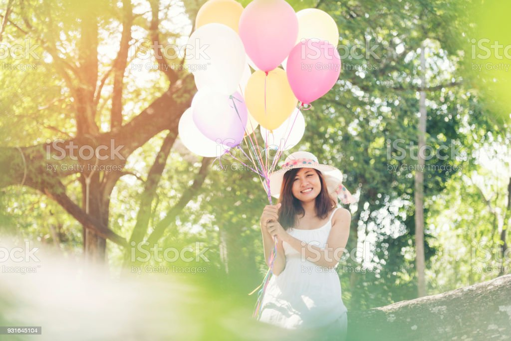 Beautiful young woman holding air balloons in garden stock photo