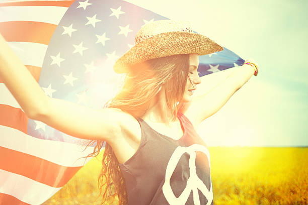 Beautiful young woman holding american flag in the wheat field stock photo