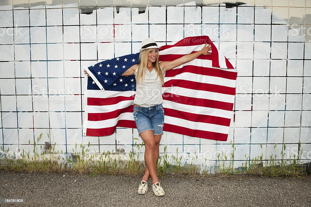 Beautiful young woman holding an american flag against wall stock photo