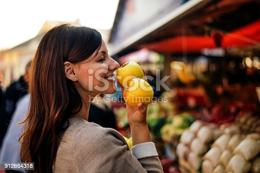 istock Beautiful young woman holding apple and smelling it with smile while standing at farmers market. 912664318